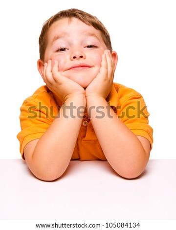 Mischievous bored child sitting at desk