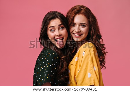 Mischievous Girl in black dress demonstrates her tongue. Ginger woman in bright yellow blouse cute smiling. Two curly ladies posing on pink background Foto stock ©