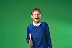 mischievous laughing schoolboy of 7 years in uniform is holding book and backpack. Isolated on green background. Back to school. child is very excited and delighted. Beginning training. Advertising.