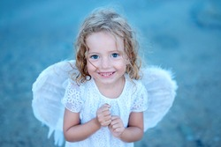 Mischievous little angel girl standing with your clenched fists. It looks like keep  fingers crossed for you.