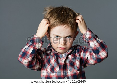 mischievous unhappy 6-year old kid with freckles scratching his hair for head lice or allergies, grey background studio