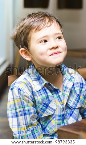 Mischievous young asian boy with a cheeky grin and dimples sitting at a table, close up upper body shot indoors