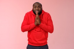 Miserable african american man beard in red hoodie stooping make supplicating upset grimace grying sobbing asking help say please hold hands pray begging mercy, apologizing need money