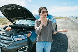 miserable asian woman traveler running into problem half way on journey is asking for roadside assistance with cell phone. bad experience of road trip with overheated car.