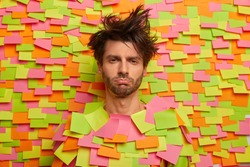 Miserable sad unshaven man feels unhappy and sleepy, expresses negative emotions, stick out head through paper background covers with various adhesive notes, has messy hairstyle after awakening