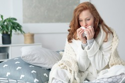 Miserable woman sitting on the bed wrapped in blanket, feeling sick with flu, having fever and blowing runny nose with handkerchief