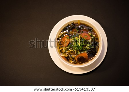 Miso soup with carrots and chive on the brown table on the black background #613413587
