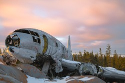 Miss Piggy Plane wreck in Churchill, Manitoba with pink, cloudy sunset background in frame with snow on rocks in front of crash landing site.