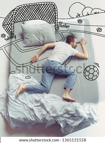 Missed football and childhood. Top view photo of young man sleeping in a big white bed at home. Dreams concept. Painted dream about sport, stadium, activity, ball, playing, team, goal, win.