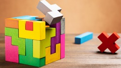 Missed items are seting in the colorful wooden cube puzzle on the brown table. Concept of decision making process, logical thinking. Geometric shapes on a wooden background.