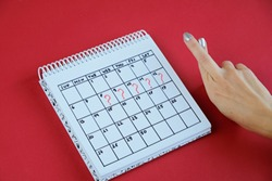Missed period marked on calendar. Woman holding fingers crossed. Unwanted pregnancy and delay in menstruation.