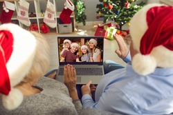 Missing children and grandchildren on Christmas holidays in lockdown. Back view of happy grandparents in Santa caps sitting on couch together, video calling their family and waving hands at screen