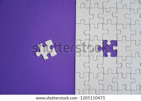 Missing jigsaw puzzle pieces. Business concept. Fragment of a folded white jigsaw puzzle and a pile of uncombed puzzle elements against the background of a Violet surface.