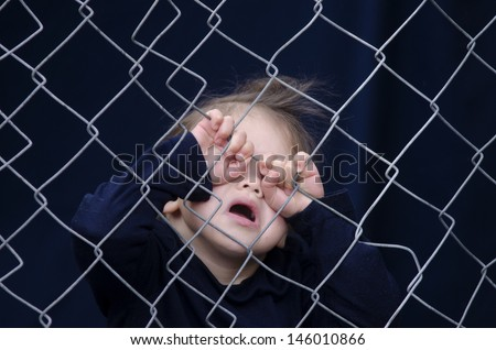 Missing kidnapped, abused, hostage, victim girl alone in emotional stress and pain, afraid, restricted, trapped, call for help, struggle, terrified, threaten, behind a fence locked in a cage cell