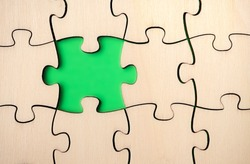 Missing puzzle piece. Almost finished, large jigsaw puzzle made of wood on green background. Concept for moving forward, understand a complicated process or filled in gaps of knowledge