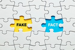 Missing puzzle pieces with the words fake versus fact. Discovering or exposing facts against fake information concept.