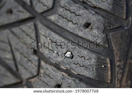 Missing spikes. Worn tire tread, winter studded tire - wheel service. Old tires cause road accidents. Old winter studded tire close up. Used snow tire with missing steal studs closeup.