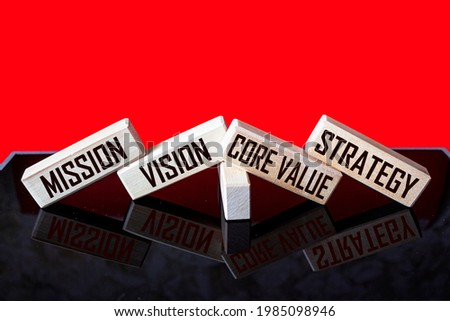 MISSION, VISION, CORE VALUE, STRATEGY A symbol of our core values. Conceptual words on wooden blocks on a black and red background. Concept of business and our core values.