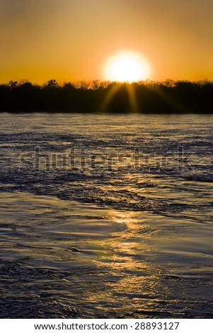 Mississippi river at flood stage with setting sun