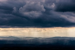 Mist and sunrays between valley and layers of mountains and hills beneath a moody, overcast sky with heavy clouds