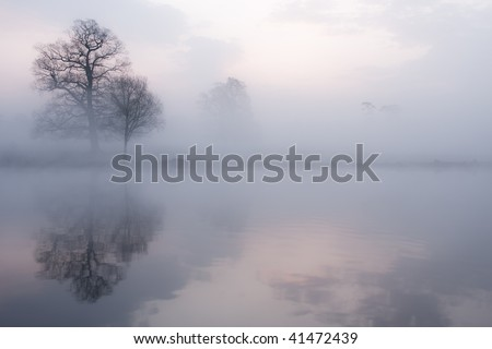 Mist on a lake at dawn with clouds reflected in the calm water