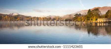 Mist rises from the calm waters of Windermere lake at Ambleside Pier, beside autumn woodland and under thew snow-capped mountains of Langdale, in England's Lake District National Park.