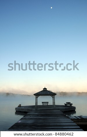 Mist rising off lake in Autumn, with dock and gazebo