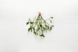 Mistletoe traditional Christmas bunch on white wooden background, flat lay, space for a greeting text