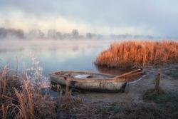 Misty autumn landscape. Plain quiet river and boat ashore.