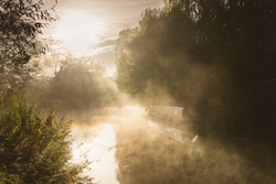 Misty autumn morning on the River Stort at Sawbridgeworth. A canal boat is moored by the riverbank and the early morning sun shines through mist.