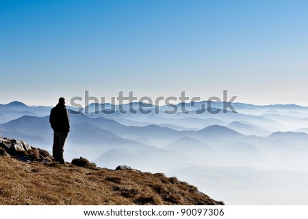 Misty autumn mountain hills and man silhouette