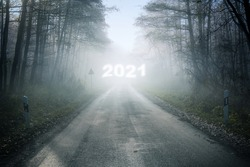 Misty country road with a blurry New Year number 2021 in the fog, leading through the forest into an uncertain future, holiday concept, copy space, selected focus
