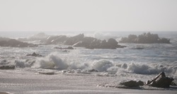 Misty, foggy day at the beach. Rough, white waves crashing against rocks on shore.