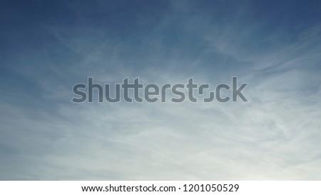 Misty foggy hazy blue sky background with high altitude clouds