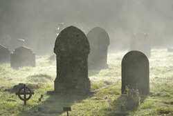 Misty graveyard,crosses and graves backlit