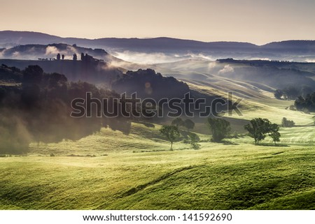 Misty hills and meadows in Tuscany at sunrise