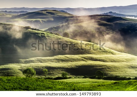 Misty hills in Tuscany at sunrise