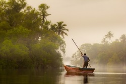 Misty morning and a man, fisherman on the boat on ethe river with