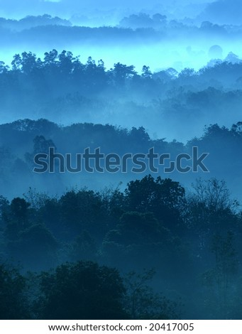 Misty morning of hilly area with ray of light.