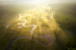 Misty morning river in sunlight. River landscape aerial view. Riverside view from above. Summer nature in sun rays. Drone view on  sunny nature with curved river. Scenery river top view.