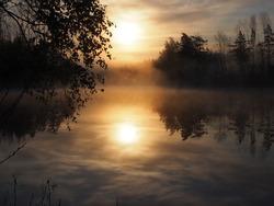 Misty morning sunrise over forest lake