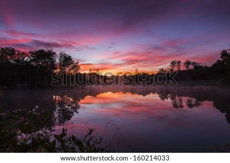 Misty morning sunrise reflection in a lake #160214033