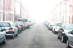 misty street with parking cars