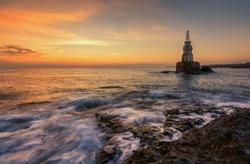 Misty sunrise of the lighthouse in Ahtopol, Bulgaria. Blue hour seascape. Long exposure