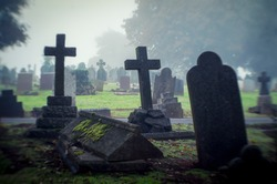 Misty view of dark stone crosses and tombstones in a deserted graveyard