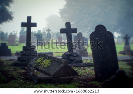 Misty view of dark stone crosses and tombstones in a deserted graveyard Stockfoto ©