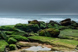 Misty Winter Morning at the Seaside - Green Mossy Rocks and Sunrise from Killcare Beach on the Central Coast, NSW, Australia.