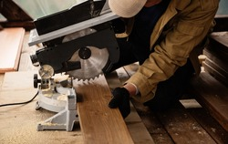 Miter saw with a large metal blade in the hands of a carpenter. Working tool for sawing wooden planks. A close-up of the sawing process. Labor protection and safety rules for the use of power tools.