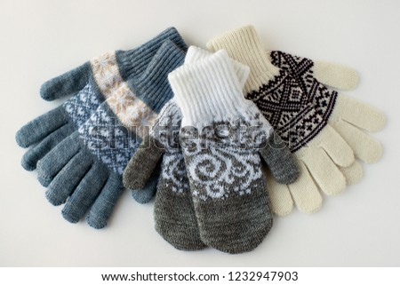 Mittens and gloves on a white background. View from above. Clothes for hands in the form of mittens and gloves. Mittens and gloves on a white background for cold seasons.