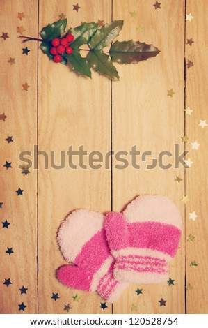 mittens, ilex and star on a wooden board